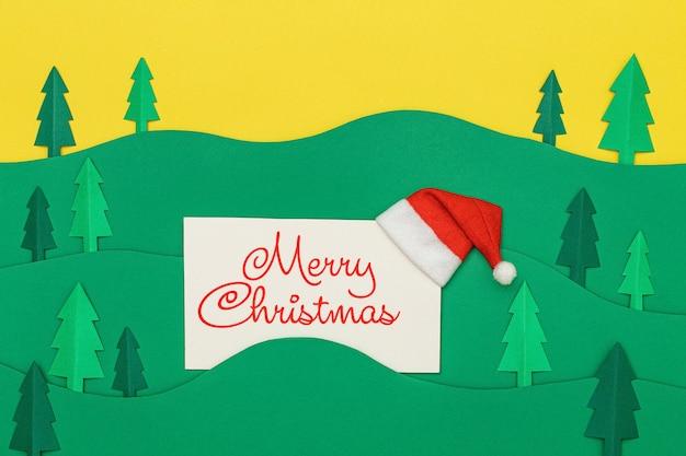 Merry christmas belettering op wenskaart met bomen boslandschap in papier knippen stijl. Premium Foto
