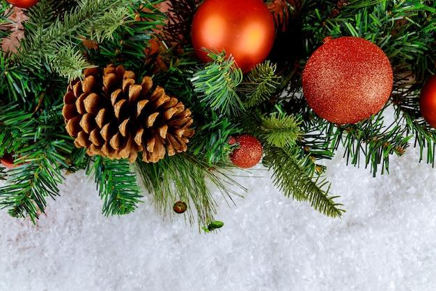 Merry christmas decoratieve bal op sneeuw met tak dennenappel kerst tijd achtergrond Premium Foto