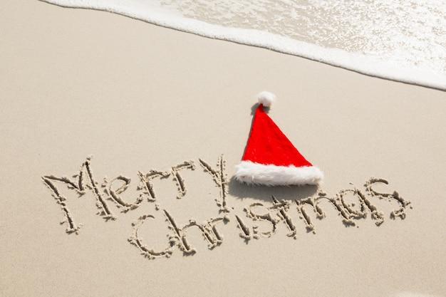 Merry christmas geschreven op zand met kerstmuts Gratis Foto