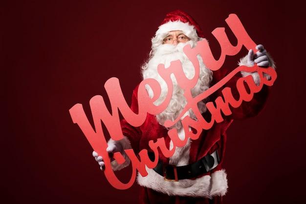 Merry christmas-teken houden door de kerstman Gratis Foto