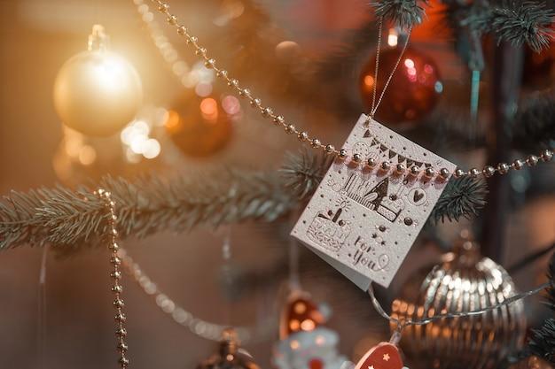 Merry x-mas, close-up van kleurrijke ballen, geschenkdoos en kerstgroet foto perceel decoratie op groene kerstboom achtergrond decoratie tijdens kerstmis en nieuwjaar. Premium Foto