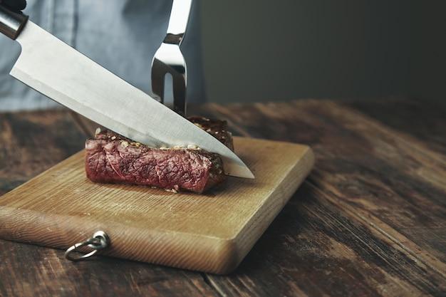Mes gesneden plakje gegrild vlees op een houten bord voor grote stalen vork in biefstuk. Gratis Foto