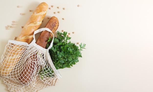 Mesh boodschappentas met vers gebakken stokbrood en peterselie bovenaanzicht met kopie ruimte Premium Foto