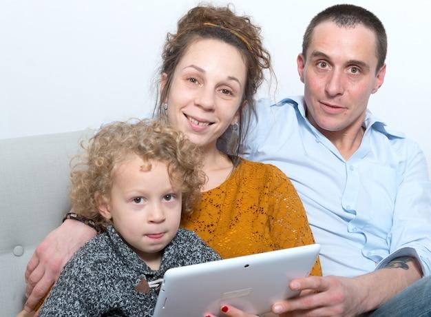 Met behulp van een tablet en gelukkige familie Premium Foto