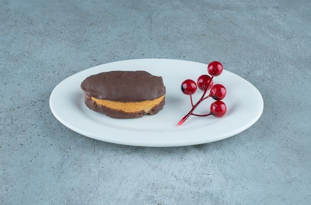 Met chocolade bedekte cake en een cluster van kerstmisbessen op een schotel op marmeren achtergrond. hoge kwaliteit foto Gratis Foto