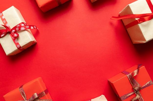 Met de hand gemaakte de giftdozen van de kerstmisambacht op rode hoogste mening als achtergrond. wintervakantie thema. plat leggen. Premium Foto