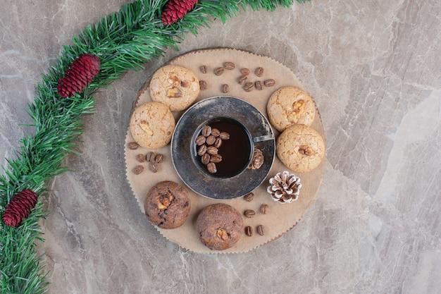 Met dennenappel versierde slinger naast een schaal met koekjes en koffie op marmer. Gratis Foto