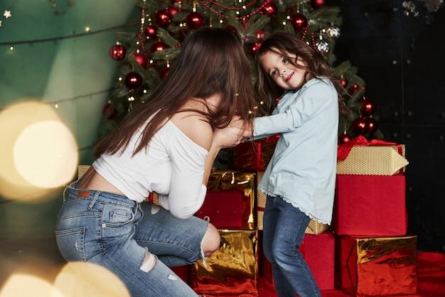 Met elkaar spelen. vrolijke moeder en dochter zitten in de buurt van de kerstboom die erachter. Premium Foto