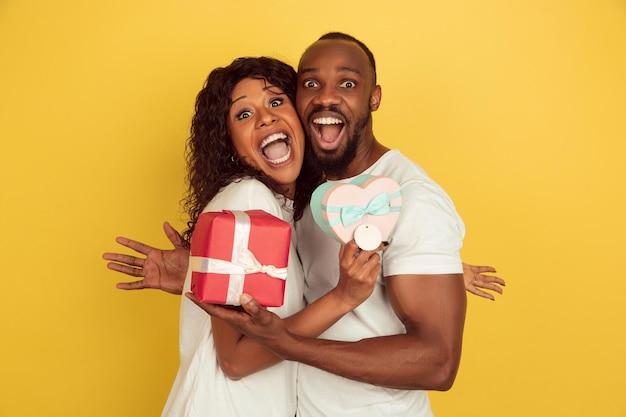 Met geschenkdozen. valentijnsdagviering, gelukkig afrikaans-amerikaans paar dat op gele studioachtergrond wordt geïsoleerd. Gratis Foto