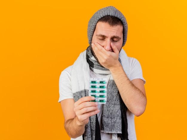 Met gesloten ogen jonge zieke man met winter hoed en sjaal hand op de mond zetten en pillen stak op camera geïsoleerd op geel Gratis Foto