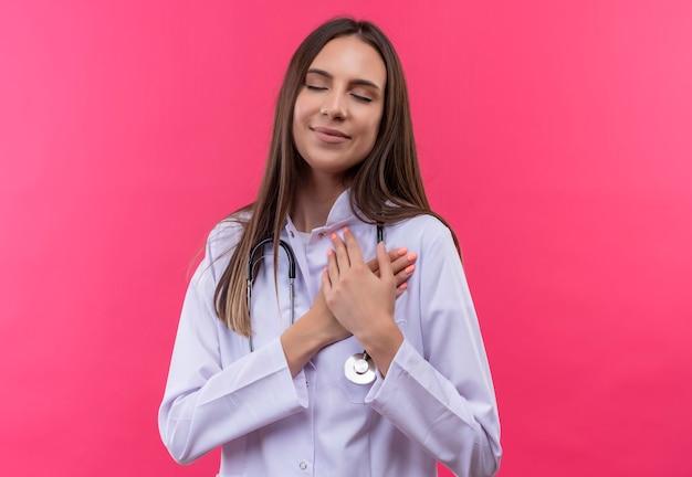 Met gesloten ogen legde het tevreden jonge doktersmeisje dat een stethoscoop medische toga draagt haar handen op het hart op geïsoleerde roze muur Gratis Foto