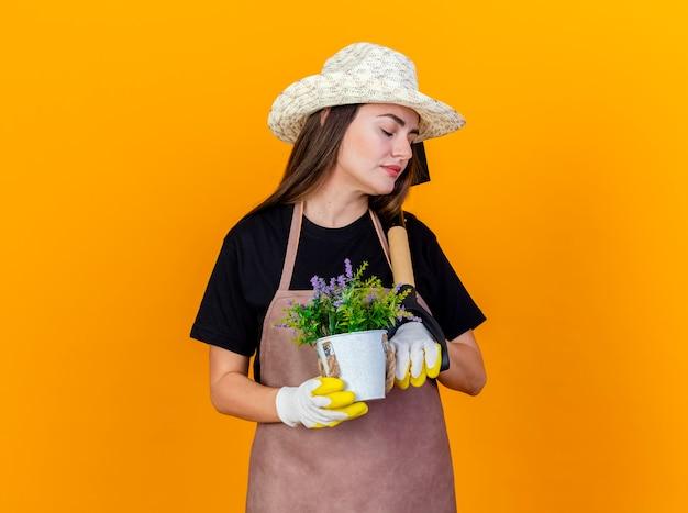 Met gesloten ogen mooi tuinman meisje uniform dragen en tuinieren hoed Gratis Foto