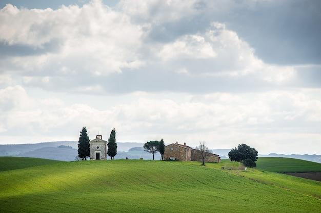 Met gras begroeid terrein met bomen en gebouwen in de verte onder een bewolkte hemel Gratis Foto