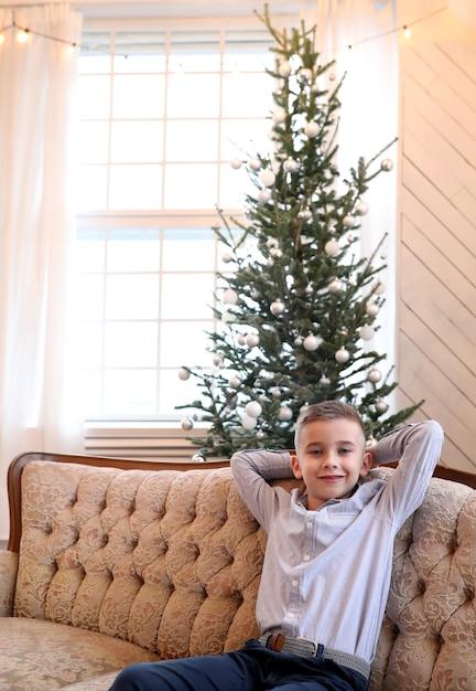 Met kerstmis zit het kind op de bank Gratis Foto