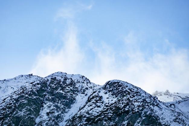 Met sneeuw bedekte bergen in de alpen. wolken die dichtbij de toppen van de bergen vliegen Premium Foto