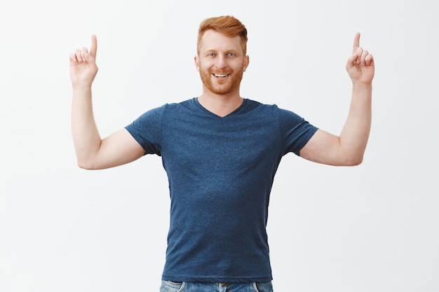 Met trots een geweldig concept naar boven laten zien. portret van knappe zelfverzekerde en gelukkige europese man met varkenshaar, handen opsteken en met tevreden en tevreden uitdrukking omhoog, zich goed voelen Gratis Foto