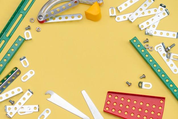 Metaal, ijzerbouwer op de gele achtergrond. onderdelen van metaalontwerper voor kinderen voor modellenwerk. Premium Foto