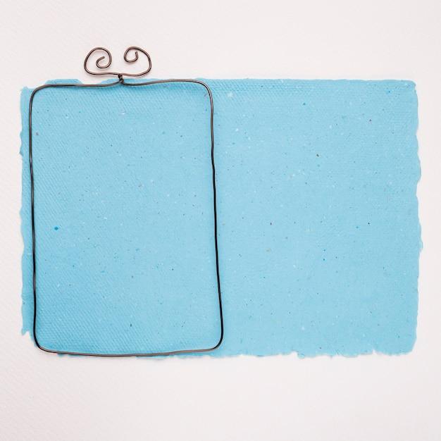 Metaal leeg kader op blauw document over witte achtergrond Gratis Foto