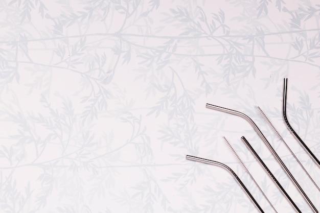 Metaalrietjes op achtergrond met bladeren Gratis Foto