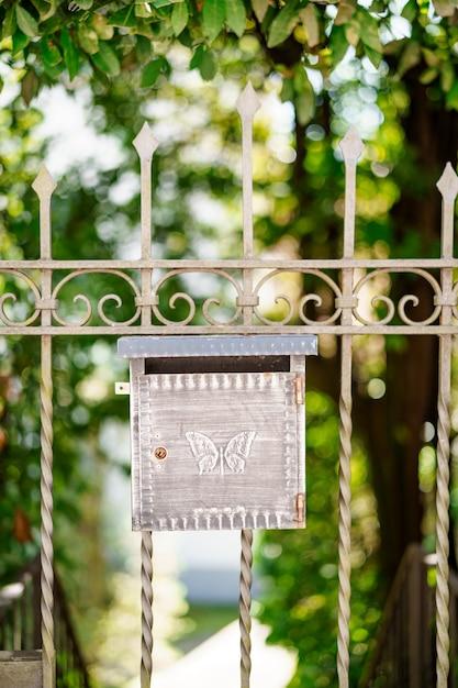 Metalen brievenbus met vlinderpatroon op de poort Premium Foto