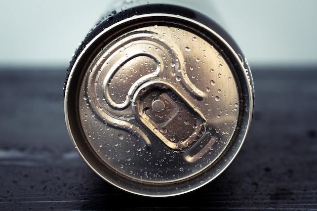 Metalen drinkblikje met waterdruppels. glanzende cola kan close-up. gouden fles drank, deksel van de verpakking van frisdrank, tonic. bovenaanzicht Premium Foto
