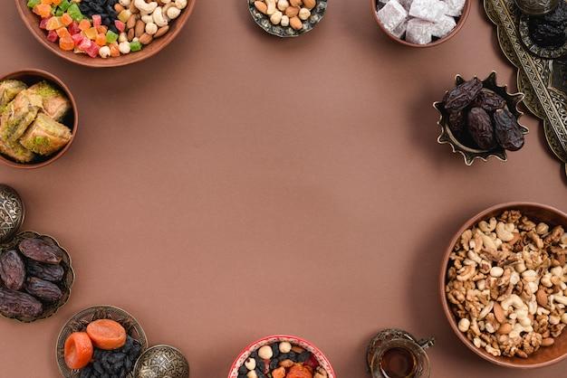 Metalen en aarden kom met gedroogde vruchten; data; lukum; noten en baklava gerangschikt op ronde vorm de bruine achtergrond Gratis Foto
