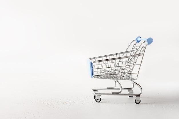 Metalen lege winkelwagen, karretje kruidenier op wit. Premium Foto
