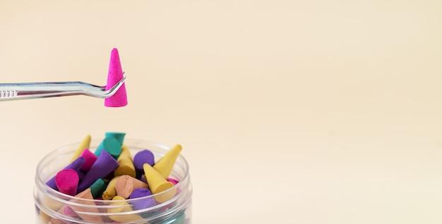 Metalen pincet met aroma-wierookkegel over fles met kleurrijke kegels. banner met kopie ruimte Premium Foto