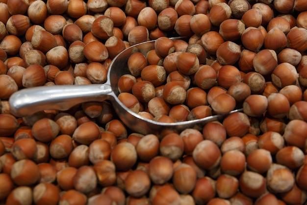 Metalen schepje in zakje met hazelnoten. hazelnoot voedsel achtergrond Premium Foto