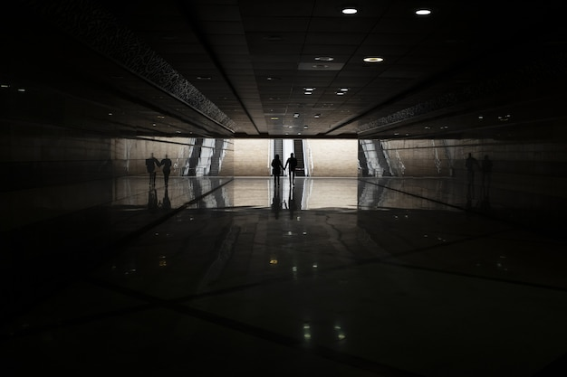 Metro donker met mensen die in de verte lopen Gratis Foto