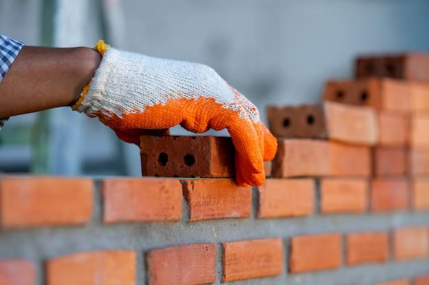 Metselaar fabrieksarbeider die metselwerk installeren op buitenmuur bij nieuw huis. Premium Foto