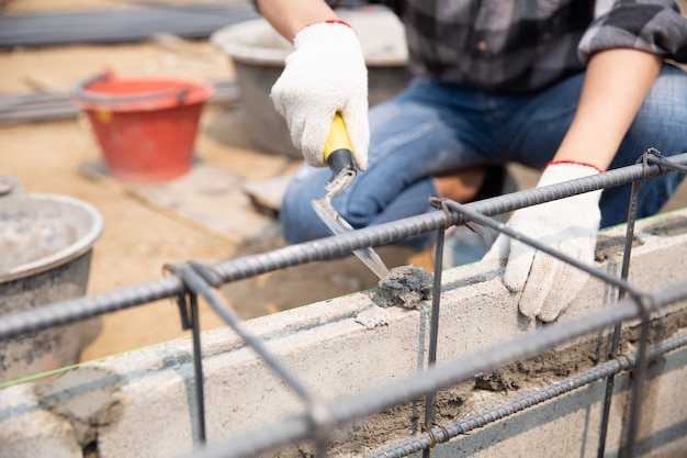 Metselaarwerknemer die baksteenmetselwerk op buitenmuur met troffelstopverfmes installeren Gratis Foto