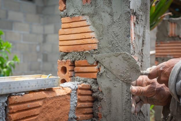 Metselen. bouwvakker die een bakstenen muur bouwt. Gratis Foto