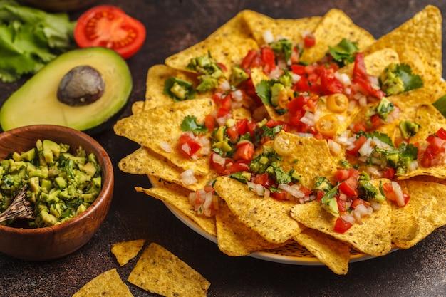 Mexicaans eten concept. nachos - gele mais totoposchips met verschillende sauzen in houten kommen: guacamole, kaassaus, pico del gallo Premium Foto