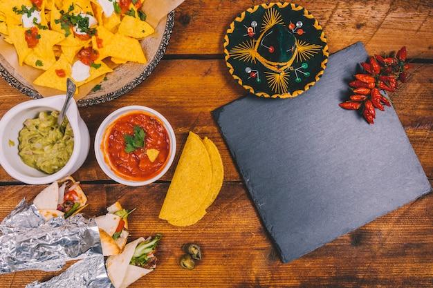 Mexicaanse hoed; ingepakte taco's; smakelijke nacho's; salsa saus; guacamole; zwarte lei en rode pepers op tafel Gratis Foto