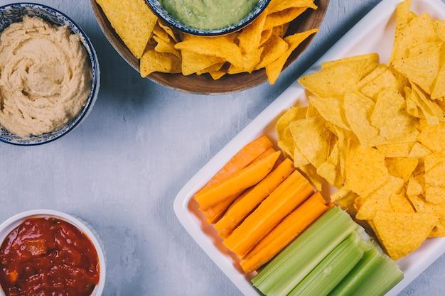 Mexicaanse nachoschips; wortel met selderiestam in dienblad met salsasaus in kom Gratis Foto