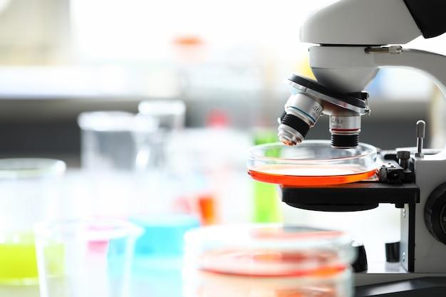 Microscoop die zich in het laboratorium van de schoolchemie onder flessen bevindt Premium Foto