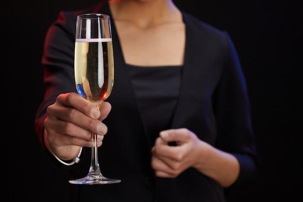 Mid sectie portret van onherkenbaar elegante vrouw met champagne glas terwijl staande tegen zwarte achtergrond op feestje, kopieer ruimte Premium Foto