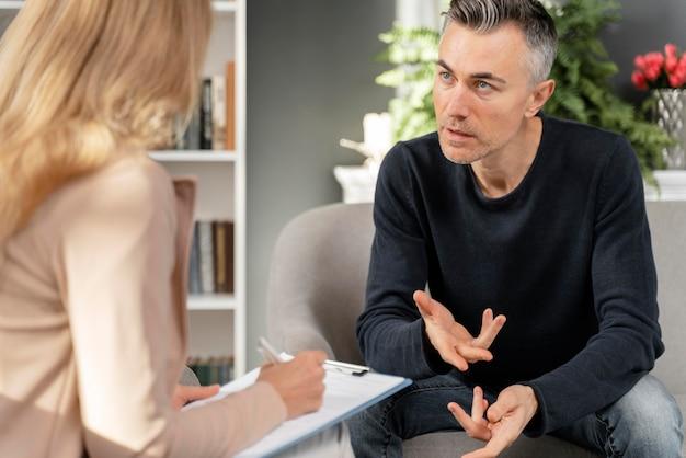 Mid shot man in gesprek met therapeut Gratis Foto