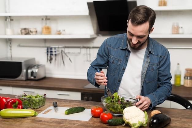 Mid shot man voorbereiding salade Gratis Foto