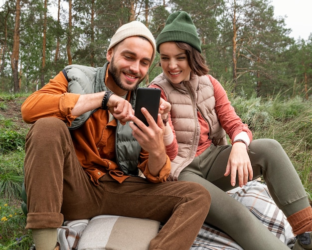 Mid shot paar zittend op het gras en kijken naar de telefoon Gratis Foto
