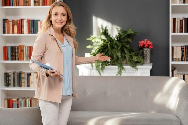 Mid shot vrouw therapeut met klembord uitnodigende patiënt in kabinet Gratis Foto