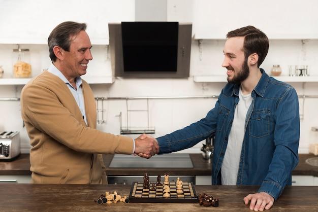 Mid shot zoon en fathe schaken in de keuken Gratis Foto