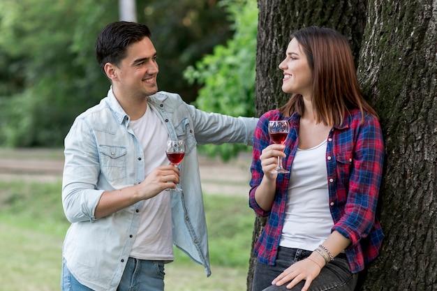Middel geschoten paar dat rode wijn in het park drinkt Gratis Foto