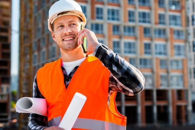 Middel geschoten portret van bouwingenieur die op de telefoon spreken Gratis Foto
