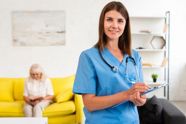 Middel geschoten vrouwelijke arts die met blauw klembord de camera bekijken Gratis Foto