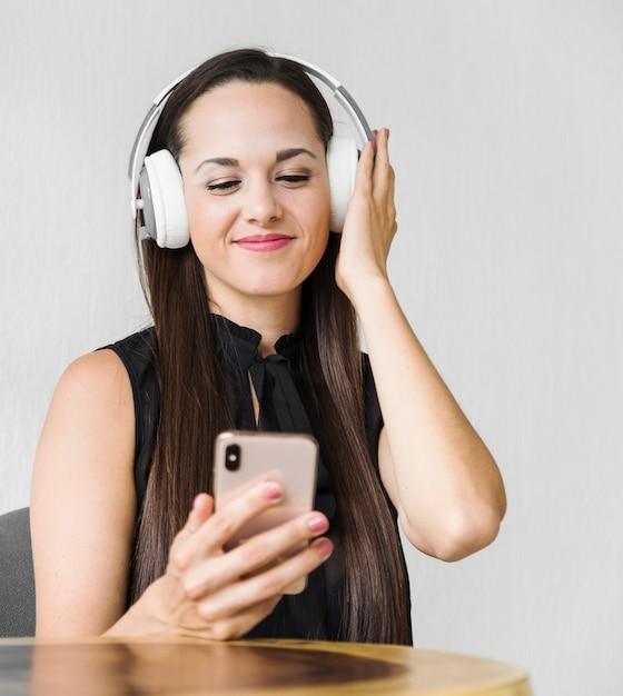 Middel geschotene bedrijfsvrouw die van wat muziek op oortelefoons geniet Gratis Foto