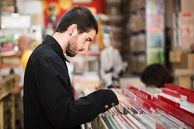 Middel geschotene zijaanzicht van de jonge mens die vinyls in opslag zoeken Gratis Foto