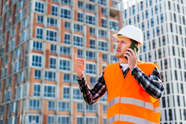 Middel geschotene zijaanzicht van ingenieur die op de telefoon spreken Gratis Foto