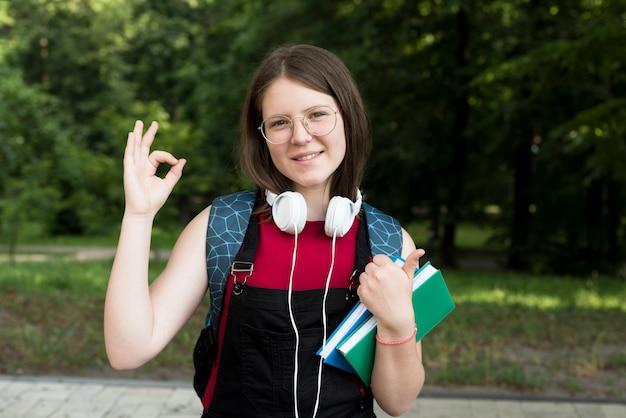 Middel van de gelukkige holdingsboeken van het middelbare schoolmeisje in handen wordt geschoten die Gratis Foto